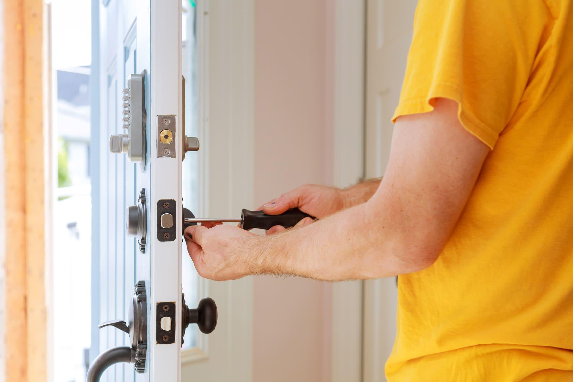 Person schraubt Schloss an der Tür an