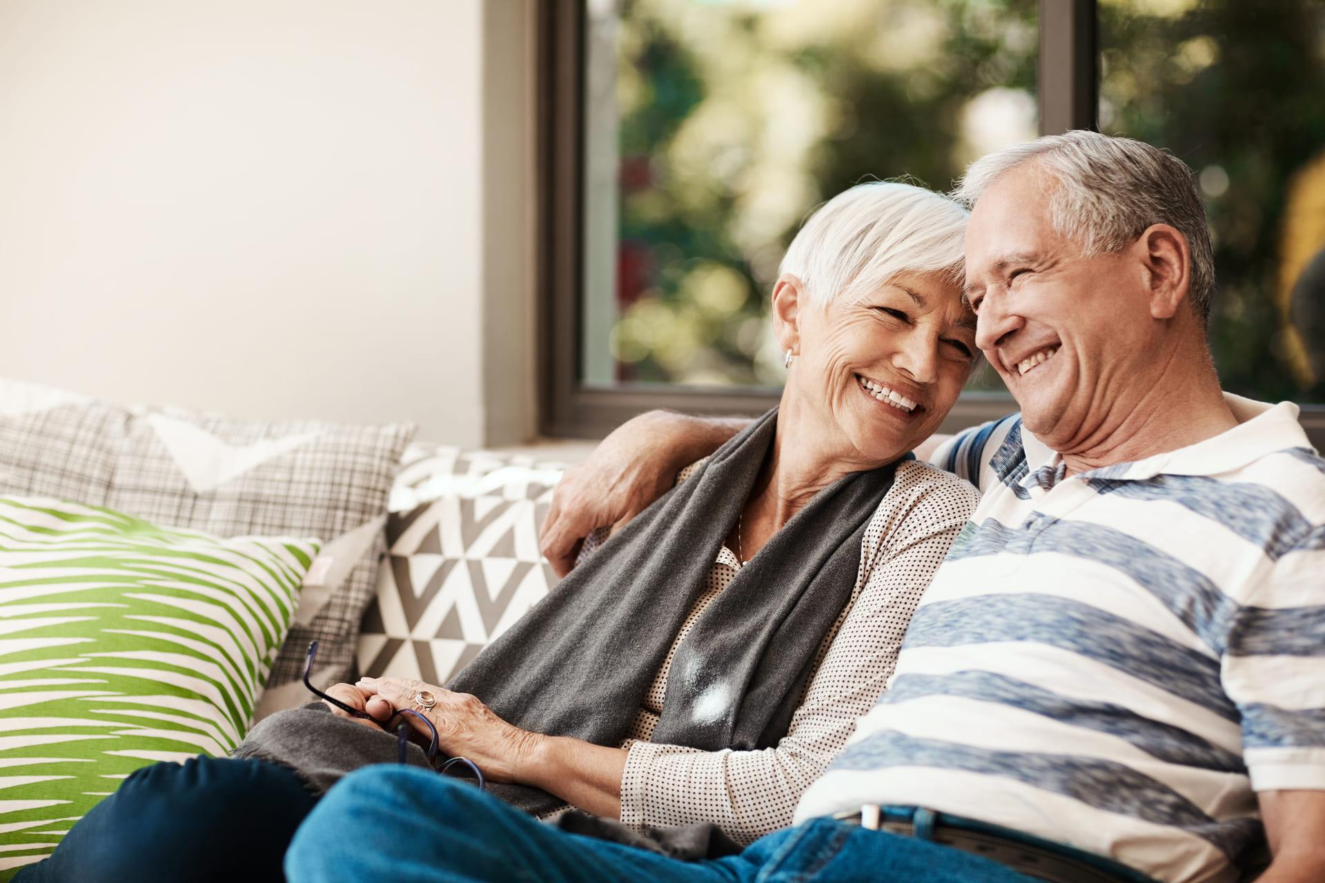 Älteres Ehepaar lacht und sitzt auf der Couch