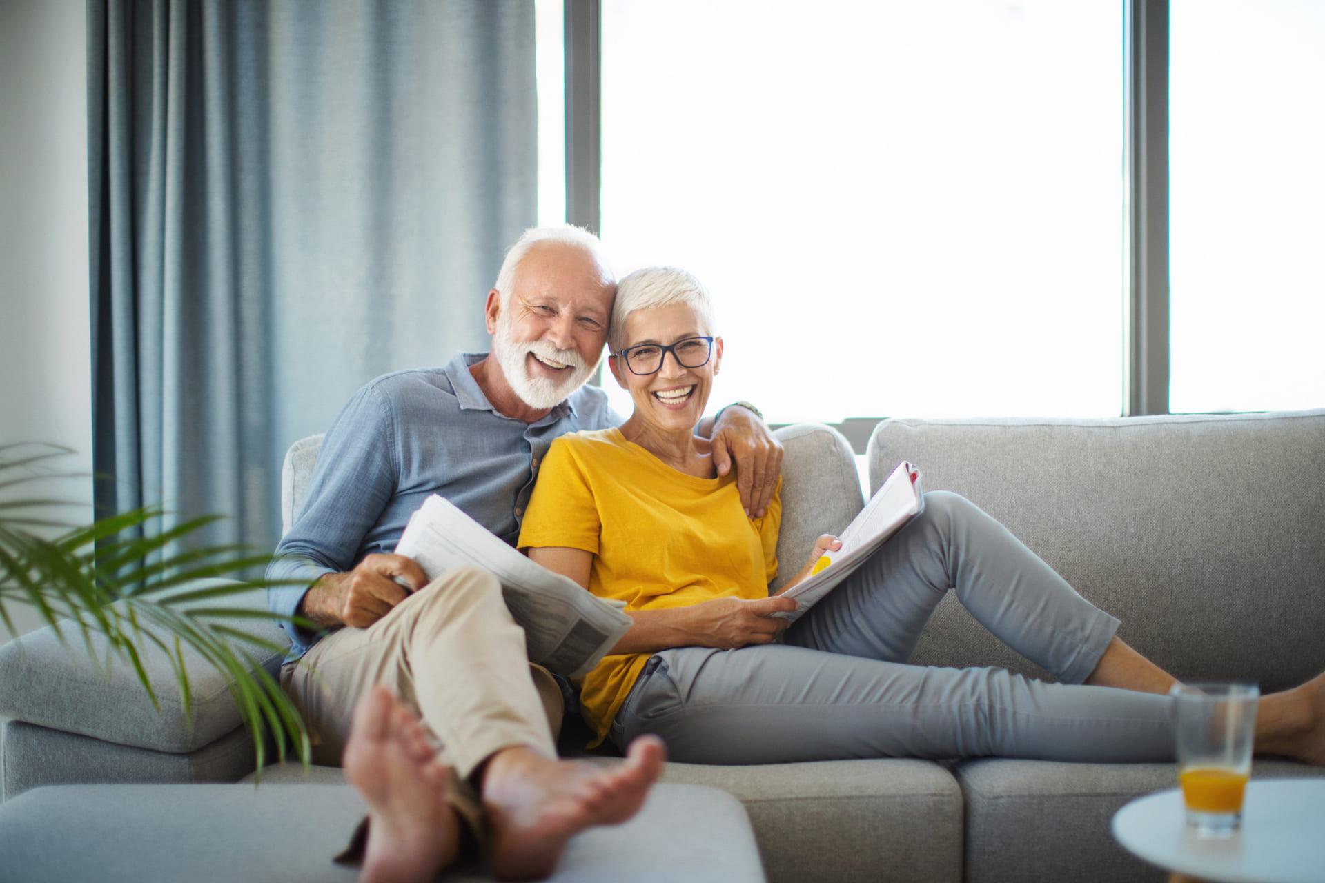 Älteres Ehepaar sitzt auf der Couch und lacht in die Kamera