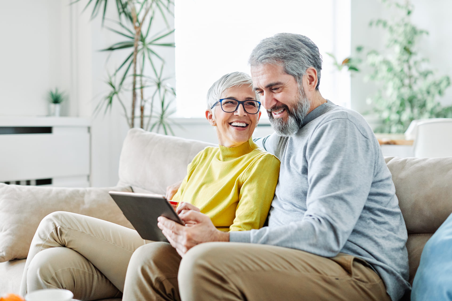 Älteres Ehepaar sitzt auf der Couch mit einem IPAD