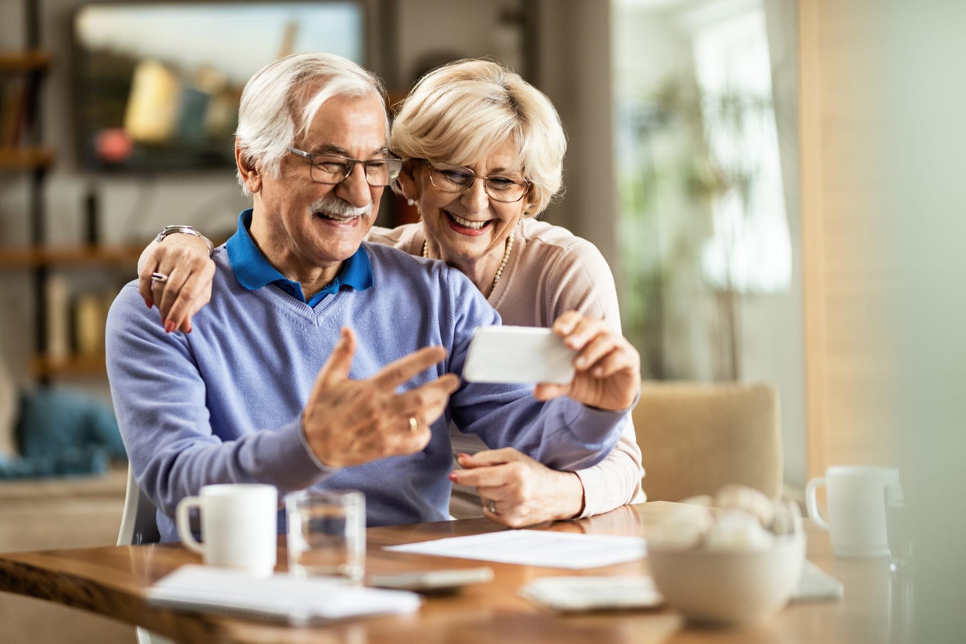 Älteres Ehepaar stehe am Tisch und schauen auf ein Handy